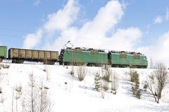Güterzug mit der elektrischen Lokomotive, die durch Eisenbahnen im Winter sich bewegt Lizenzfreie Stockbilder