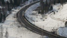 Güterzug mit Frachtanhängerbewegungen durch den Winterwald stock footage