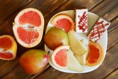 G?bka torty, plasterki grapefruitowy i bonkrety k?amaj? w bia?ym talerzu na drewnianej powierzchni robi? sosnowe deski Bufet w au obrazy stock