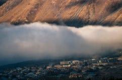Gęsta chmura nad Stepantsminda Kazbegi wioską przeciw górze, Gruzja Fotografia Stock