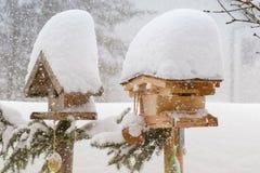 Gęsty śnieżny spadać na dachu drewniany ptasi dozownik podczas zimy ja zdjęcia stock
