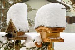 Gęsty śnieżny spadać na dachu drewniany ptasi dozownik z Pospolitym bla Fotografia Stock