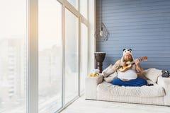 Gęsty facet bawić się gitarę w domu Fotografia Stock