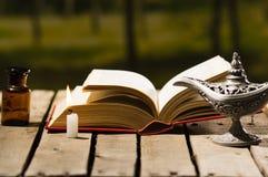 Gęsty książkowy lying on the beach otwarty na drewnianej powierzchni, Aladin lampie i wosk świeczki obsiadaniu, obok go, piękny n Fotografia Royalty Free