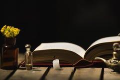 Gęsty książkowy lying on the beach otwarty na drewnianej powierzchni, małej brown butelce z, kwiatami, Aladin stylowymi lampami i Zdjęcie Stock