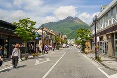 Główna droga od dworca wypełniającego z ludźmi, streetscape i lokalni sklepy, kierujemy świeży zielony Yufudake halny szczyt, błę zdjęcia royalty free