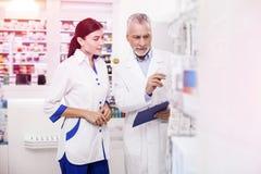 Główna farmaceuta pomaga młodemu improver z produktami zdjęcia royalty free
