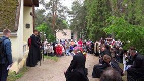 Główny ksiądz w soutane i wierzący grupy ludziach klęczy i ono modli się blisko kaplicy zbiory wideo