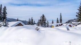 Głębocy śnieg paczki nakrycia domy i drogi wysokogórska wioska słońce Osiągają szczyt zdjęcia royalty free