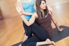 Głęboka rozciągliwości joga praktyka: dwa wielokulturowej młodej dziewczyny ćwiczy joga: instruktor i uczeń Zdjęcie Stock