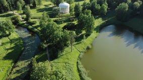 Głęboka rzeka odbija zielone drzewne sylwetki przy białym gazebo zbiory