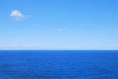 Głęboki błękitny denny nawadnia i jasny niebo Fotografia Stock