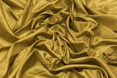 Gładka elegancka złocista jedwabiu lub atłasu luksusowa sukienna tekstura może używać a fotografia royalty free