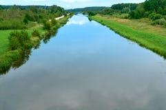 Gładki kanał z odbiciem niebo, długa rzeka z porosłymi zielonymi bankami, sztuczny staw Obrazy Royalty Free