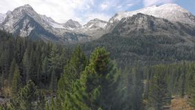Gładkie, bezzałogowe kinowe wzgórza z śniegiem, powietrzny widok śnieżnych szczytów góry Latające za drzewami lub sosnami zdjęcie wideo