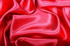 Gładzi elegancką czerwoną jedwabiu lub atłasu teksturę jako tło Obrazy Royalty Free
