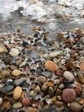 Gładzi kamienie obramowanych w lodzie na skalistej linii brzegowej w zimie zdjęcia stock