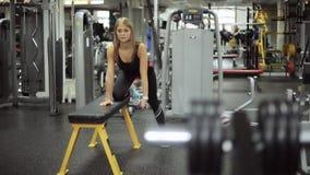 Gładzi ostrość na kobiecie angażującej w gym z dumbbells przy ławką zbiory wideo