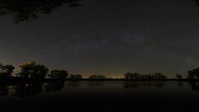 Gładzi powierzchnię lasowy jezioro na tle nocne niebo a Obrazy Stock
