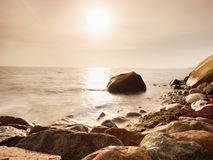 Głazy przy wyspa brzeg wtykają up od gładkiego morza Kamieniści wybrzeży igrania fala zdjęcia stock