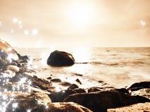 Głazy przy wyspa brzeg wtykają up od gładkiego morza Kamieniści wybrzeży igrania fala ocean obraz stock