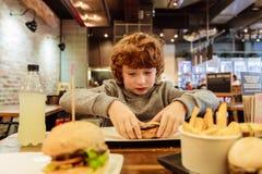 Głodna chłopiec je hamburger w restauraci fotografia stock