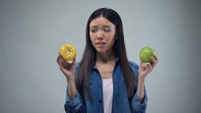 Głodna dziewczyna próbuje wybierać między pączkiem i jabłkiem, zdrowy łasowanie, kuszenie zbiory