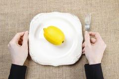 Głodna kobiety łasowania cytryna Symbol przystosowanie nowa kultura Fotografia Royalty Free