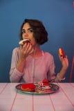 Głodni młodej dziewczyny łasowania donuts przy stołem Zdjęcia Stock
