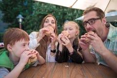 Głodni rodzinni łasowanie hamburgery, siedzi przy stołem w fast food restauraci zdjęcia stock