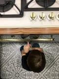 Głodny chłopiec obsiadanie obok piekarnika w kuchni fotografia stock