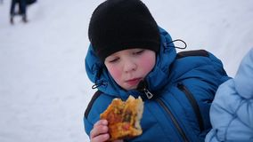 Głodny dziecko je pizzę wewnątrz outdoors kwiat czasu zimy śniegu zbiory wideo