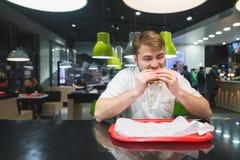Głodny mężczyzna je fast food przy restauracją Mężczyzna greedily je hamburger przy stołem przy tacą Fasta food pojęcie Zdjęcie Royalty Free