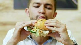 Głodny mężczyzna je soczystego hamburger w fast food restauracji, wyśmienicie jedzenie zbiory wideo
