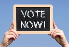 Głosowanie Teraz - kobieta wręcza mienia chalkboard z tekstem Obraz Royalty Free