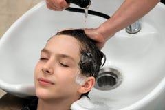 Głowa facet z jego przygląda się zamkniętych kłamstwa nad zlew, gdy kobieta myje jego głowę w piękno salonie Żeńskie ręki zdjęcia royalty free