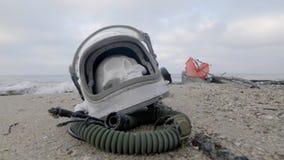 Głowa nieżywy kosmonauta kłama na piasku morzem Astronauta rozbijający na jego statku kosmicznym Chmurna pogoda wiatr zbiory wideo