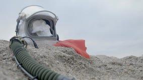 Głowa nieżywy kosmonauta kłama na piasku morzem Astronauta rozbijający na jego statku kosmicznym Chmurna pogoda wiatr zdjęcie wideo