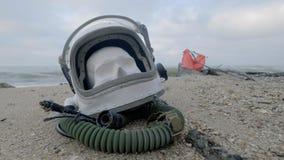 Głowa nieżywy kosmonauta kłama na piasku morzem Astronauta rozbijający na jego statku kosmicznym Chmurna pogoda wiatr zbiory