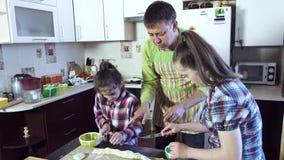 Głowa rodzina uczy jego córki rżnięty ciasto w kawałki prawidłowo zbiory