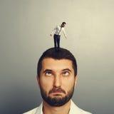 Głupi mężczyzna z małym mężczyzna na głowie fotografia stock