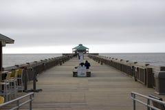 Głupota Plażowy Południowa Karolina, Luty 17, 2018 - kobieta siedzi samotnie na boardwalk ławce na chmurzącym dniu fotografia stock