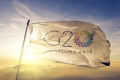 G20 2018年阿根廷旗子纺织品挥动在顶面日出薄雾雾的布料织品 图库摄影