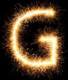 G för alfabet för tomteblossfyrverkeriljus på svart Royaltyfria Foton