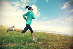 G fitness woman runner running on beautiful trail in grassland Stock Image