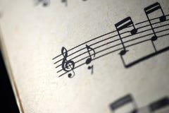 G-klav och musikaliska anmärkningar i den gamla musikaliska anteckningsboken Fotografering för Bildbyråer