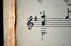 G-klav och musikaliska anmärkningar i den gamla musikaliska anteckningsboken Royaltyfria Foton