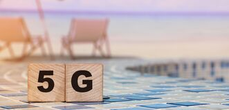 5G letters on wood blocks on swimming pool borders and beach. Big data concept