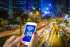 5G of LTE-presentatie Vrouwenhand die smartphone met moderne stad op de achtergrond gebruiken Stock Afbeelding