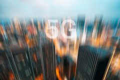 5G on a motion blurred city skyline. Illuminated at dusk royalty free stock image